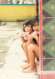 Two girls eating in Solo. Barefooted kids - indonesian girls sitting on porch and eating in Solo (Java, Indonesia royalty free stock image