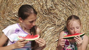 Two girls eating watermelon near the haystack. Young happy children sitting on the field, behind haystack, eating watermelon.Summer vacation stock footage