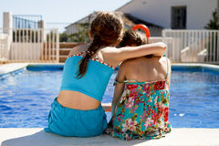 Two girls ebracing by the pool. Two sisters ebracing each other by the pools edge Stock Images