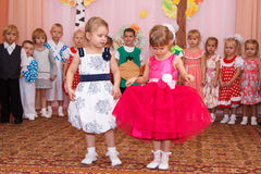 Two girls in elegant dresses read poetry at children's holiday Stock Images