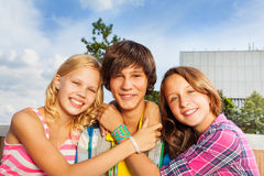 Two girls embracing boy's neck and smile happily Stock Photo