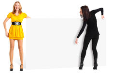 Two girls with empty publicity board. Stock Image