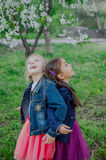 Two girls enjoying falling petals in spring garden royalty free stock photo