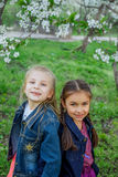 Two girls enjoying falling petals in spring garden stock photo