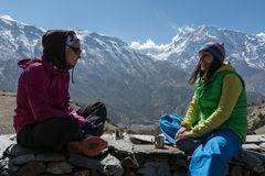 Two girls enjoying tea or coffee on Annapurna trek circuit, Nepa Royalty Free Stock Photography