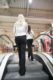 Two girls on escalators Stock Photography