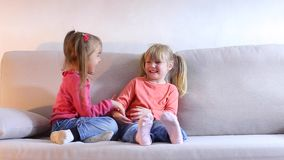 Two little girls play and have fun on couch in living room.n. Two girls of European appearance playing, laughing and having fun on couch in living room, children stock footage