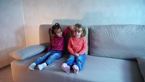 Two sisters sitting on couch, little girl cries. Two girls from European family sit in living room on couch, younger child upset and weep, older sister comforts stock footage