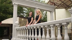Two girls in evening dresses stand near fence. Two luxurious girls in evening dresses are standing near a stone vintage fence stock video footage