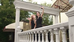 Two girls in evening dresses taking selfies. Two sexy girls in black long evening dresses take a selfie standing near a beautiful fence stock video