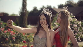 Two girls in evening gowns and crowns make selfie. On phone in garden with roses stock footage