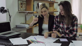 Two girls examine and discussing some charts sitting at a desk in the office stock video footage