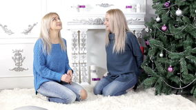 Two girls exchanging Christmas gifts. Two young, blond hair, women woman, lady, ladies exchanging giving each other Christmas presents, gifts. Smiling, being stock footage