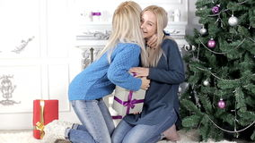 Two girls exchanging Christmas presents. Two young, blond hair, women woman, lady, ladies exchanging giving each other Christmas presents, gifts. Smiling, being stock video footage