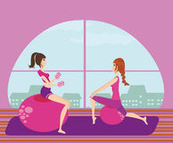 Two girls exercising with Pilates fit balls. Royalty Free Stock Photos