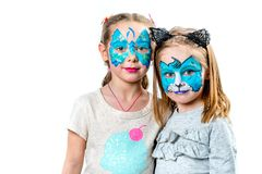 Two girls with face paintings. Portrait of two cute girls with face painting of a tiger and butterfly isolated on white background. Little girls with face art royalty free stock photography