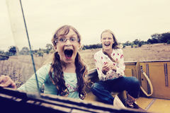 Two girls at the farm. Two girls enjoying the ride in the back of dad's ute Royalty Free Stock Photos