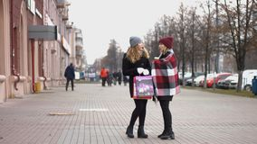 Two girls after the festive shopping consider the gifts. Slow motion. Two young pretty girls stand on the street and holding bags with shopping stock video