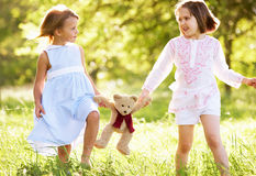 Two Girls In Field Carrying Teddy Bear Stock Photo