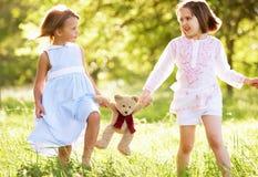 Two Girls In Field Carrying Teddy Bear Stock Photo