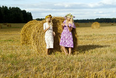 Two girls in a field near haystacks Royalty Free Stock Photos
