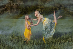 Two girls in the field. One girl levitates. royalty free stock photo