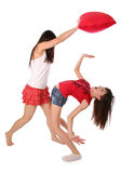 Two girls fighting on the pillows. Isolated at white background Stock Photo