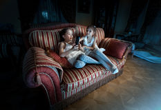 Two girls fighting for TV remote on sofa at night Stock Photo