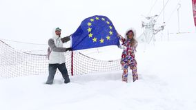 Two girls with the flag of the European Union on the ski slope. Two girls with the flag of the EU against the background of the ski slope stock video