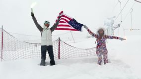 Two girls with the flag of the United States. And multi-colored falshfeyer against the background of the ski slope stock footage