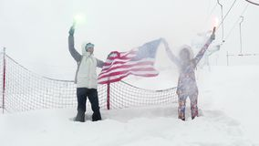 Two girls with the flag of the United States. And multi-colored falshfeyer against the background of the ski slope stock video