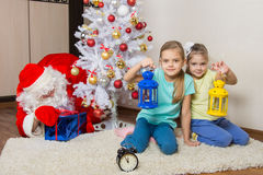 Two girls with flashlights waiting for Santa Claus at the Christmas tree in New Years Eve Royalty Free Stock Images