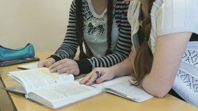 Two girls flip pages of textbook at lesson. Two girls sitting at the desk flip the pages of textbook at the lesson stock footage