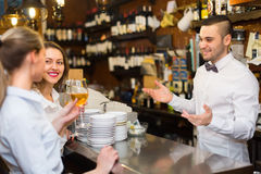 Two girls flirting with barman Royalty Free Stock Image