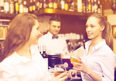 Two girls flirting with barman. Two beautiful girls flirting with handsome barman royalty free stock images