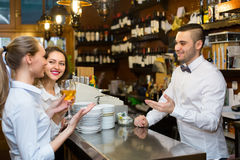 Two girls flirting with barman Royalty Free Stock Photography