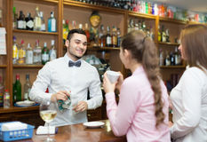 Two girls flirting with barman Royalty Free Stock Photos