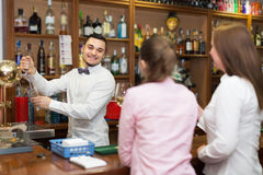 Two girls flirting with barman Stock Images