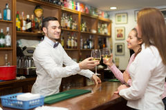 Two girls flirting with barman Royalty Free Stock Images