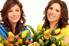 Two girls with flowers Stock Image