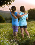 Two girls flowers field at sunset. Two girls hugging in flowers in field at sunset Stock Image