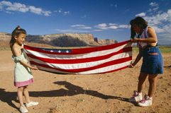 Two girls folding the American flag, Royalty Free Stock Photography