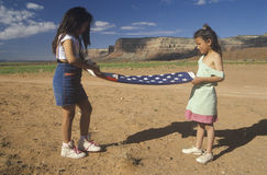 Two girls folding the American flag, Royalty Free Stock Photo