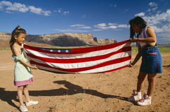 Two girls folding the American flag, Lee Ranch, UT Stock Photo