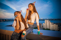 Two girls are fooled with festive pipes. On the day of birth Royalty Free Stock Photo