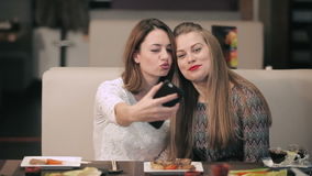 Two girls fooling around while doing selfie. Two girls friends taking various funny selfie pictures in Japanese restaurant. Two pretty girls sitting together in stock video footage