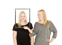 Two girls and a frame Royalty Free Stock Photos
