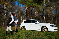 Two girls friend and stylish white sports car royalty free stock image