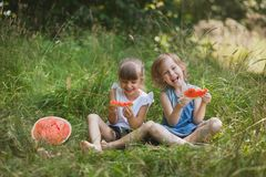 Two girls friends eating watermelon and having fun outdoor stock images