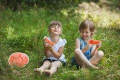 Two girls friends eating watermelon and having fun outdoor royalty free stock photos